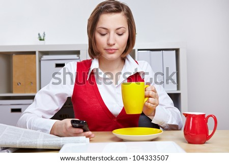 Woman in office taking a break with cup of coffee and smartphone - stock photo