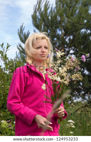 Woman in outdoors cutting wild flowers - stock photo