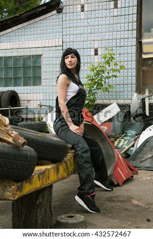 woman in overalls sits near a warehouse of scrap and wheels outdoors - stock photo