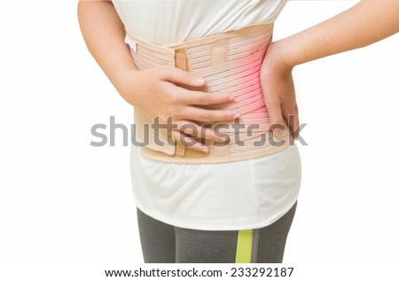 Woman in pain from back injury wearing lumbar brace corset  - stock photo