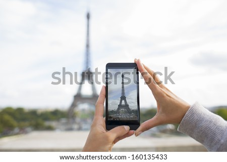 Woman in Paris taking pictures with a Cell phone in front of Eiffel Tower - stock photo