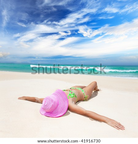 Woman in pink hat lies on the beach - stock photo