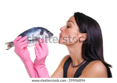 Woman in pink rubber gloves about to kiss a fish, isolated on white background. - stock photo