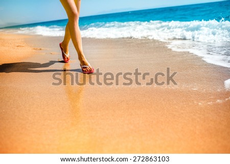 Woman in pink slippers running on the sandy beach - stock photo