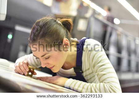 Woman in printing house using magnifying glass  - stock photo