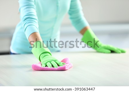 Woman in protective gloves cleaning kitchen table with rag - stock photo