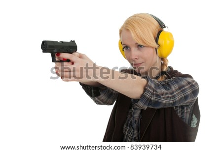 woman in protective receivers aiming a pistol at shooting range - stock photo