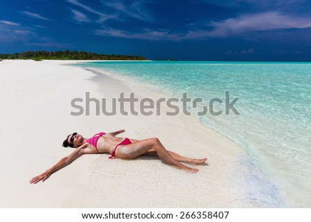 Woman in purple and red bikini stretched on the sandy beach - stock photo