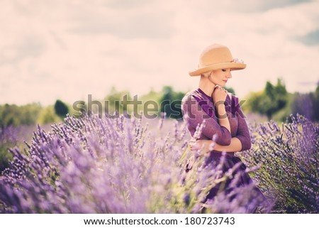 Woman in purple dress and hat in lavender field  - stock photo
