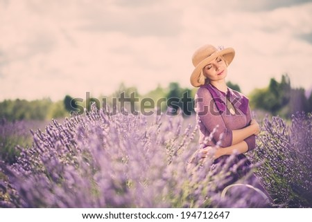 Woman in purple dress and hat with basket in lavender field  - stock photo