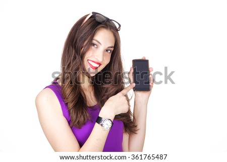 Woman in purple tank top happy smiling and pointing on her mobile phone. Fit and athletic Caucasian brunette girl posing on white background. - stock photo