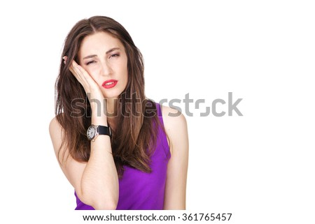 Woman in purple tank top having strong tooth pain and holding her head with a hand. Fit and athletic Caucasian brunette girl posing on white background. - stock photo