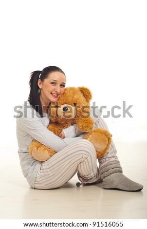 Woman in pyjama sitting on floor and hugging teddy bear - stock photo
