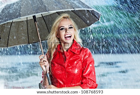 Woman in raincoat smiling as she holds umbrella - stock photo