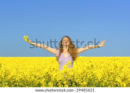 woman in rapeseed (canola) field enjoying the open air - stock photo