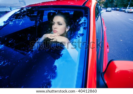 woman in red car dreams of future - stock photo