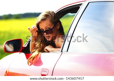 woman in red car get out window - stock photo