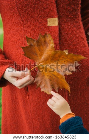 Woman in red coat holding yellow leaf - stock photo