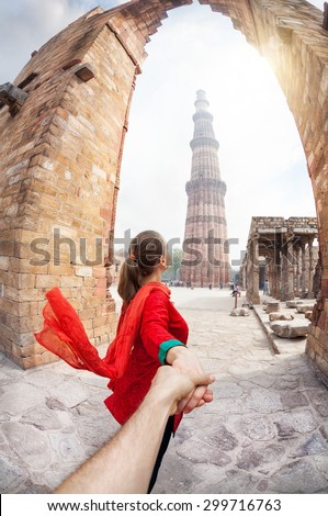 Woman in red costume leading man by hand to Qutub Minar tower in Delhi, India - stock photo
