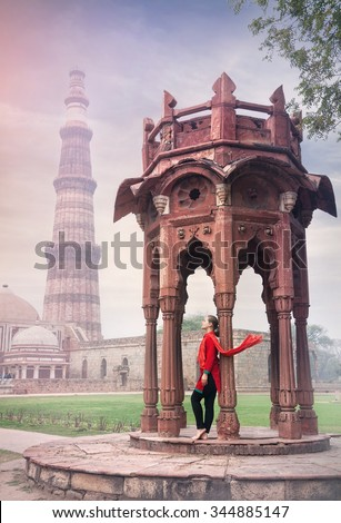 Woman in red costume with scarf standing near old architecture of Qutub Minar tower in Old Delhi, India - stock photo