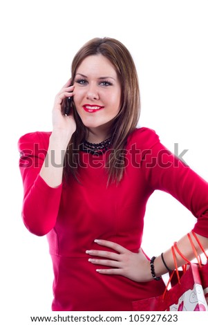 Woman in red dress with shopping bags, smiling and looking directly at the camera while talking on her cellphone - stock photo