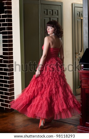 Woman in red evening dress at the door (turning round) - stock photo