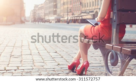 Woman in red high-heeled shoes and dress using digital tablet. Beautiful sexy business woman enjoying sunny morning in the city, sitting on the bench, browsing Internet and drinking coffee. Lens Flare - stock photo