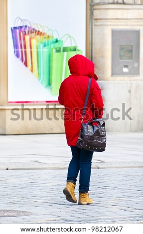 Woman in red jacket with shopping bags in the background - stock photo