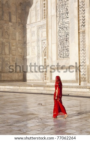 Woman in red saree/sari walking past the Taj Mahal. - stock photo