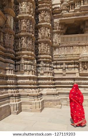 Woman in red sari at Khajuraho Temple. Madhya Pradesh, India. - stock photo