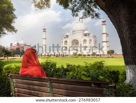 Woman in red scarf sitting on the bench in the shadow and looking at Taj Mahal in Agra, Uttar Pradesh, India - stock photo