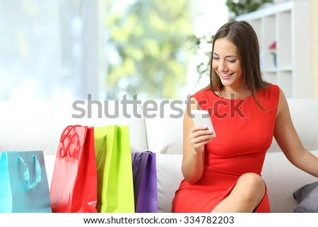 Woman in red using a smart phone with shopping bags beside - stock photo