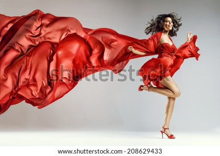 Woman in red waving dress with flying fabric - stock photo