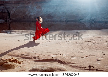 Woman in red waving dress with flying fabric runs on the background of sands career - stock photo