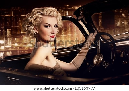 Woman in retro car against night city. - stock photo