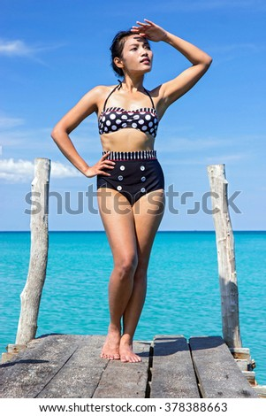 woman in retro swimsuit posing on the mole over sea - stock photo