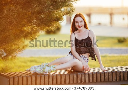 woman in roller skates sitting on a bench on it wearing a blue shirt and light in the form of chert skating dresses prohodile in the city park around the growing fir - stock photo