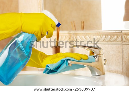 woman in rubber gloves with rag and detergent cleaning the bathroom - stock photo
