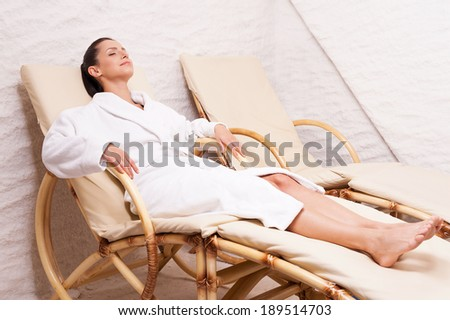 Woman in salt room. Beautiful young woman in bathrobe relaxing in salt room  - stock photo