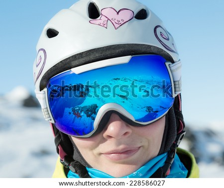 Woman in ski goggles, which reflect the mountains. - stock photo