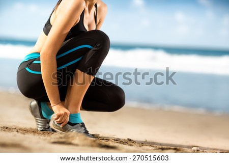 woman in sports clothes tying shoelaces before running on beach  - stock photo