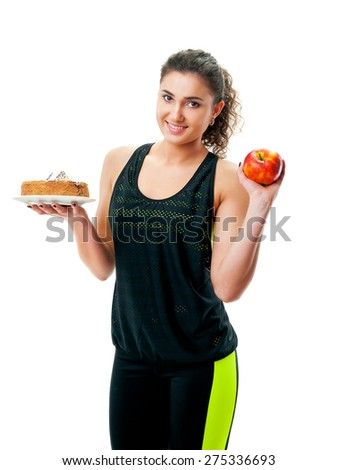 woman in sportswear holding a cake and apple - stock photo