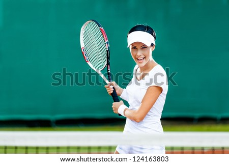 Woman in sportswear plays tennis at competition - stock photo