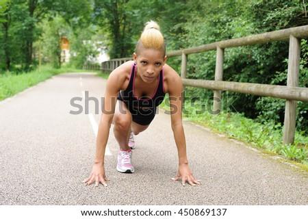 Woman in start position preparing to run - stock photo