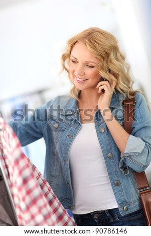 Woman in store talking with girlfriend on the phone - stock photo
