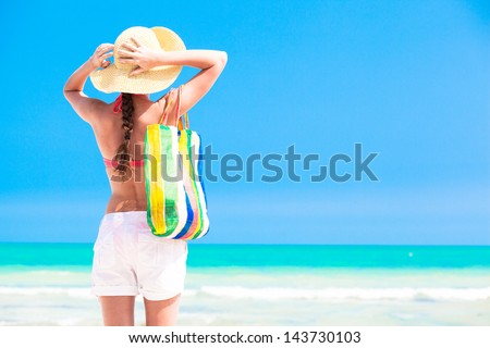 Woman in straw hat and on a tropical beach with bag - stock photo