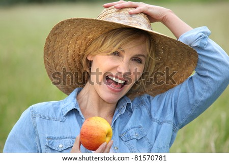 Woman in straw hat eating apple - stock photo