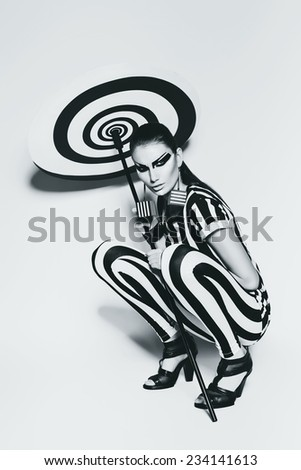 woman in striped top and leggings sitting with umbrella in studio - stock photo