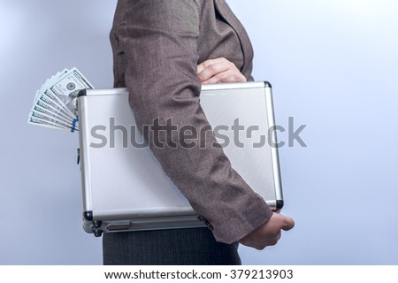 Woman in suit carries metal briefcase with dollars on grey background.  Conception of safe storage and protection of cash. Financial theme. Horizontal view. - stock photo