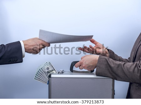 Woman in suit gives metal briefcase with dollars, man gives her important documents. Conception of safe storage and protection of cash, the exchange process. Financial theme. Horizontal view. - stock photo
